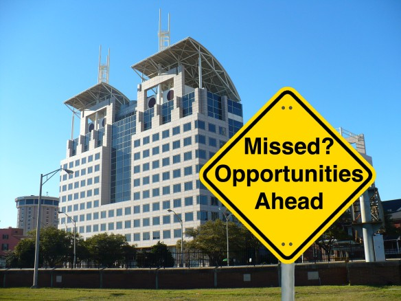 "A yellow Caution road sign reading ""Missed? Opportunities Ahead"" in the foreground of a picture of Mobile Government Plaza"